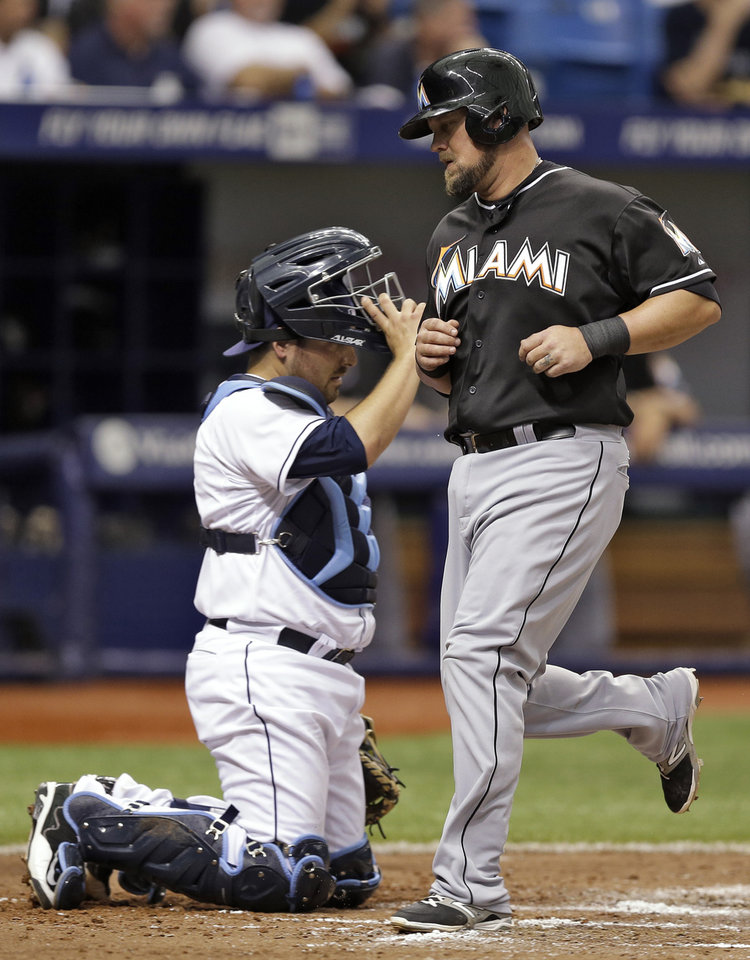 Photo - Miami Marlins' Casey McGehee, right, scores in front of Tampa Bay Rays catcher Ali Solis on an RBI single by Marcell Ozuna during the fourth inning of an interleague baseball game Thursday, June 5, 2014, in St. Petersburg, Fla. (AP Photo/Chris O'Meara)