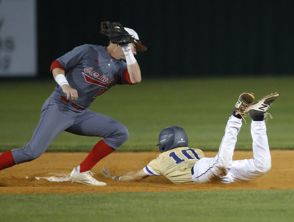 Photo - Heritage Hall's Colby Lewis steals second as Verdigris's Kade Keith tries to place a tag in the first inning during the high school baseball playoff game between Heritage Hall and Verdigris at Edmond Santa Fe High School in Edmond, Okla., Thursday, May 10, 2018. Photo by Sarah Phipps, The Oklahoman