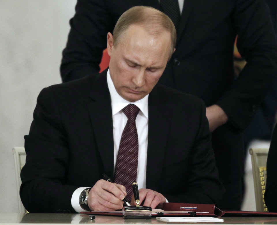 Photo - Russian President Vladimir Putin signs a treaty for Crimea to join Russia during a signing ceremony after his addressing the Federal Assembly in the Kremlin in Moscow,  Tuesday, March 18, 2014. President Vladimir Putin on Tuesday signed a treaty to incorporate Crimea into Russia, describing the move as the restoration of historic injustice and a necessary response to what he called the Western encroachment on Russia's vital interests.(AP Photo/Alexander Zemlianichenko)