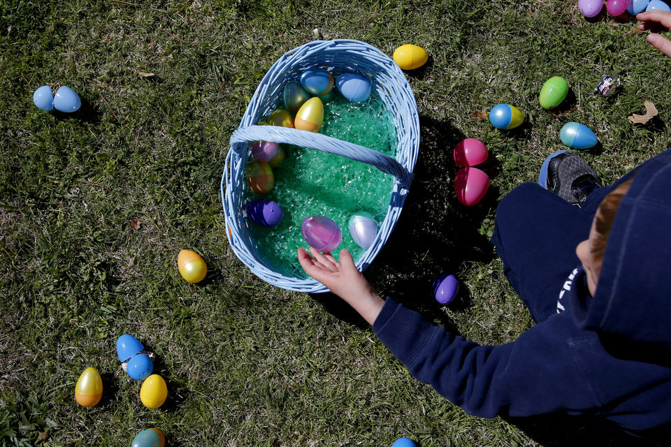 Photo -  A child collects eggs during a past egg hunt at New Covenant United Methodist Church's Easter Egg Hunt and Spring Carnival in Edmond. [Bryan Terry, The Oklahoman Archives]