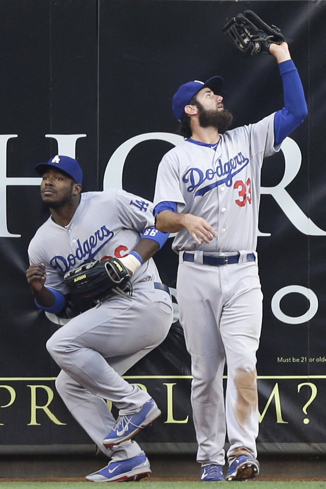 Photo - Los Angeles Dodgers center fielder Scott Van Slyke (33) catches a fly ball hit by Cincinnati Reds' Donald Lutz as right fielder Yasiel Puig avoids a collision in the fourth inning of a baseball game, Monday, June 9, 2014, in Cincinnati. (AP Photo/Al Behrman)