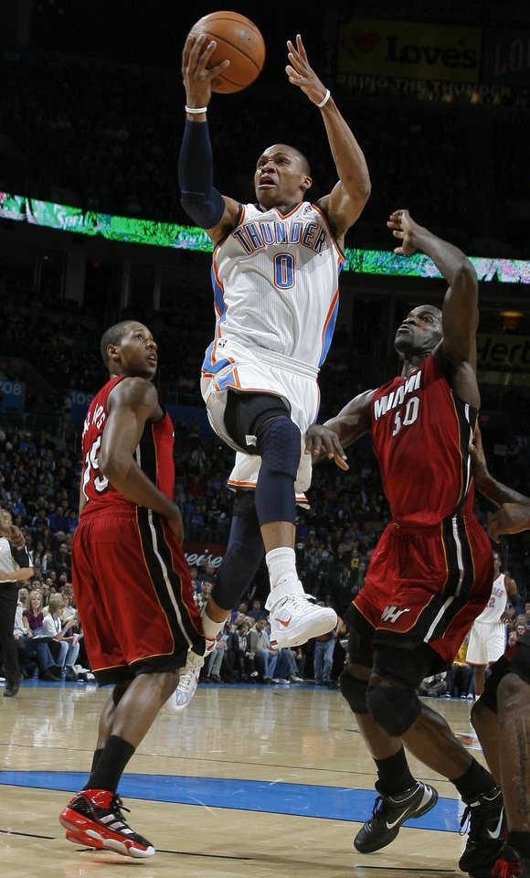 Photo - Oklahoma City's Russell Westbrook (0) shoots in between Miami's Mario Chalmers (15) and Miami's Joel Anthony (50) and during the NBA basketball game between Oklahoma City and Miami at the OKC Arena in Oklahoma City, Thursday, Jan. 30, 2011. Photo by Sarah Phipps, The Oklahoman