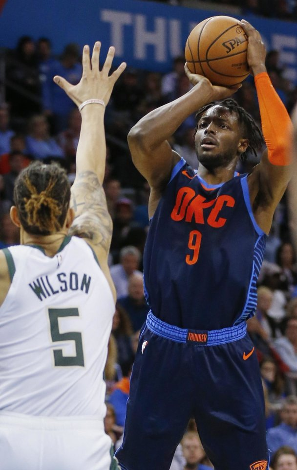Photo - Oklahoma City's Jerami Grant (9) shoots against Milwaukee's D.J. Wilson (5) during an NBA basketball game between the Milwaukee Bucks and the Oklahoma City Thunder at Chesapeake Energy Arena in Oklahoma City, Sunday, Jan. 27, 2019. Oklahoma City won 118-112. Photo by Nate Billings, The Oklahoman