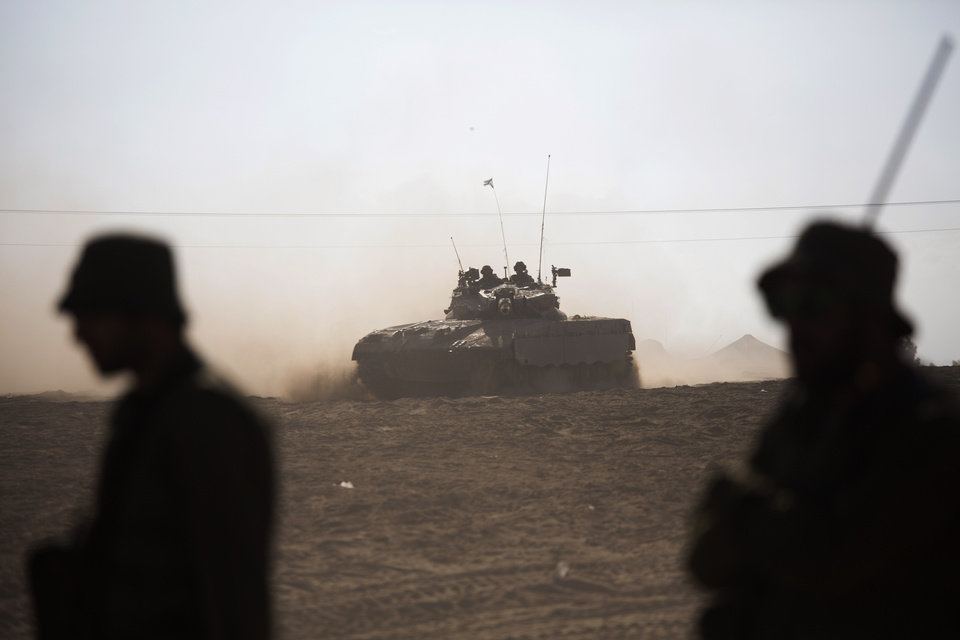 Photo - Israeli tank rides near the Israel and Gaza border Friday, July 25, 2014. Early Friday, Israeli warplanes struck tens of houses throughout the Gaza Strip as international efforts continue to broker a cease fire in the 18 day-old war. (AP Photo/Dusan Vranic)