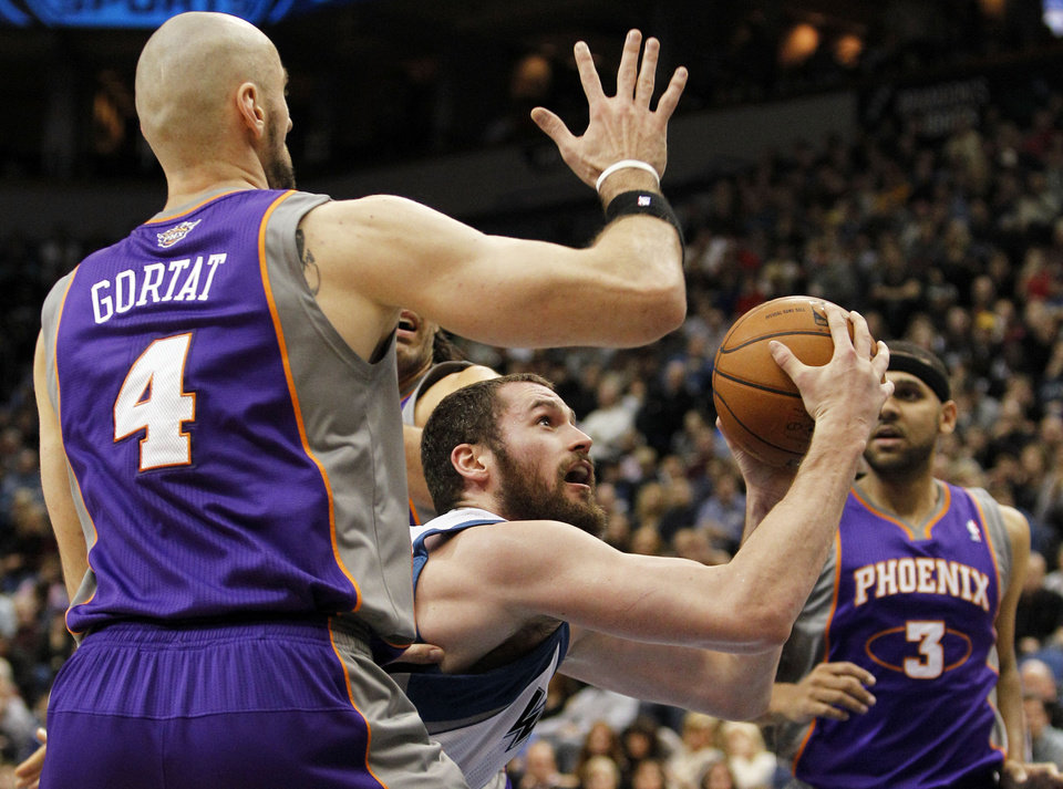 Minnesota Timberwolves forward Kevin Love, center, is fouled on his way to the basket by Phoenix Suns center Marcin Gortat (4) as Suns guard Jared Dudley (3) looks on during the first half of an NBA basketball game, Saturday, Dec. 29, 2012, in Minneapolis. (AP Photo/Genevieve Ross)