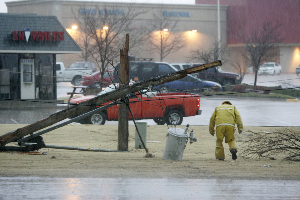 An OG&E worker walks under a downed power line near Northwest Expressway and Rockwell in Oklahoma City, Oklahoma February 10, 2009.  BY STEVE GOOCH, THE  OKLAHOMAN