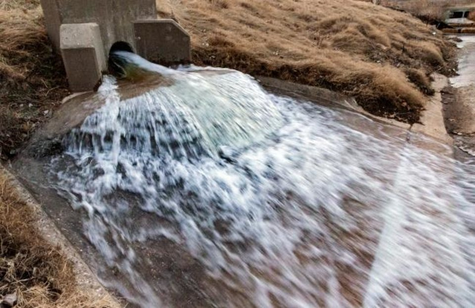 Photo -  Water flows into the drainage ditch as crews work to drain the mile-long Bricktown Canal in Oklahoma City, Okla Tuesday, Jan. 21, 2020. The canal holds 3 million gallons of water, and will take up to two weeks to clean out the silt and debris.   [Chris Landsberger/The Oklahoman]