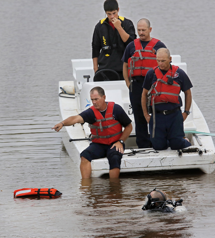 Photo -  Oklahoma City Fire Department divers assist Thursday afternoon in locating and removing a truck from the Oklahoma River. A person at the Chesapeake Boathouse reported seeing the vehicle roll down a ramp into the water under the Byers Avenue bridge near SE 6. Divers located the truck after a short search and attached a cable to the truck so it could be removed from the river. No one was inside the truck when it was recovered. Photo by Jim Beckel, The Oklahoman   Jim Beckel -