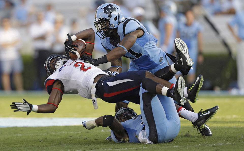 Photo - Liberty's D.J. Abnar (2) is tackled by North Carolina's Malik Simmons (11) and Sam Smiley during the first half of an NCAA college football game in Chapel Hill, N.C., Saturday, Aug. 30, 2014. (AP Photo/Gerry Broome)
