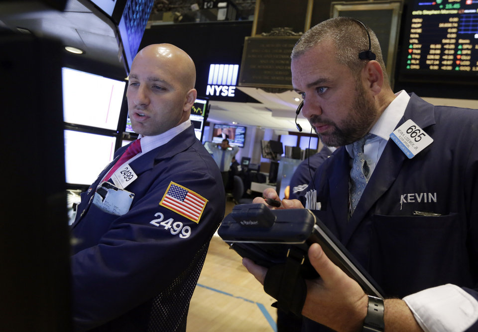 Photo - Specialist John Parisi, left, and trader Kevin Lodewick work on the floor of the New York Stock Exchange, Tuesday, Aug. 19, 2014. Better news on home building and corporate earnings are sending stocks higher. (AP Photo/Richard Drew)