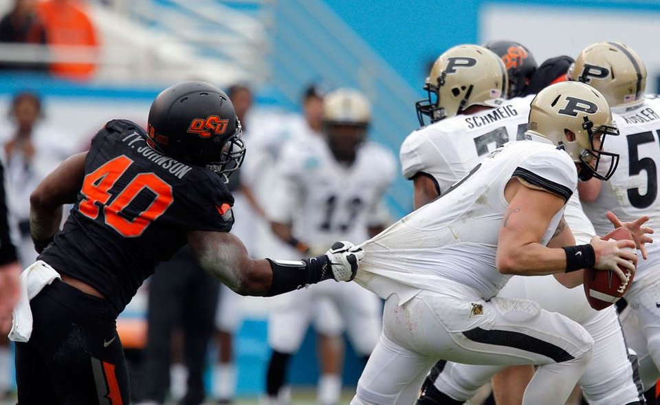 Oklahoma State's Tyler Johnson (40) pulls down Purdue's Robert Marve (9) during the Heart of Dallas Bowl football game between Oklahoma State University (OSU) and Purdue University at the Cotton Bowl in Dallas,  Tuesday, Jan. 1, 2013. Photo by Sarah Phipps, The Oklahoman