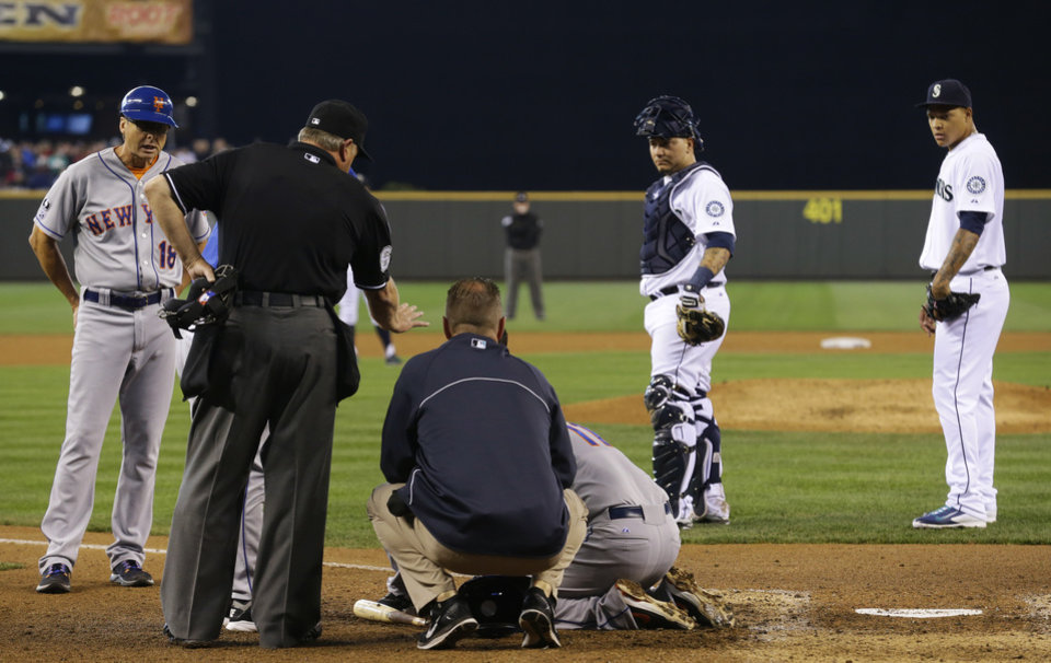 Photo - Coaches and trainers attend to New York Mets' Ruben Tejada at he kneels at the plate after being hit in the batting helmet by Seattle Mariners starting pitcher Taijuan Walker, right, in the fifth inning of a baseball game, Wednesday, July 23, 2014 in Seattle. Tejada left the game and did not complete his at-bat. (AP Photo)