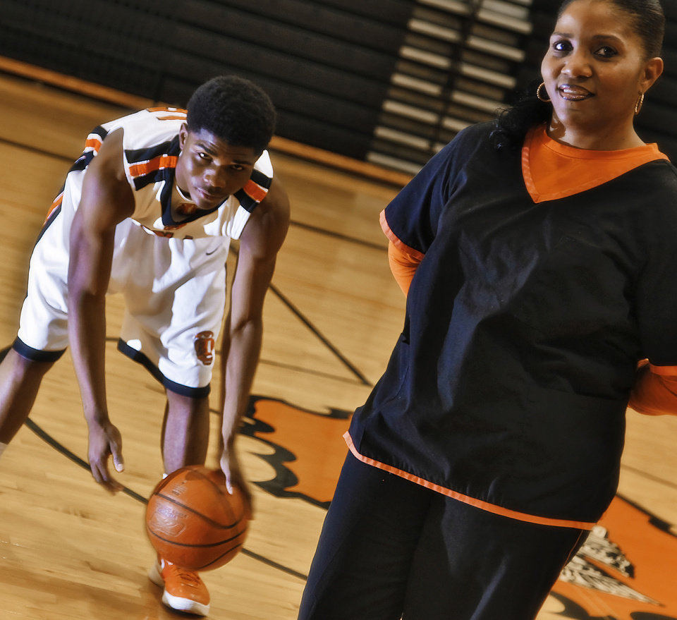 Photo - HIGH SCHOOL BASKETBALL / DORSHELL CLARK: Douglass High School junior Stephen Clark poses with a photo with his mother Dorshell at the high school gym on Wednesday, Feb. 8, 2012, in Oklahoma City, Okla.  Photo by Chris Landsberger, The Oklahoman