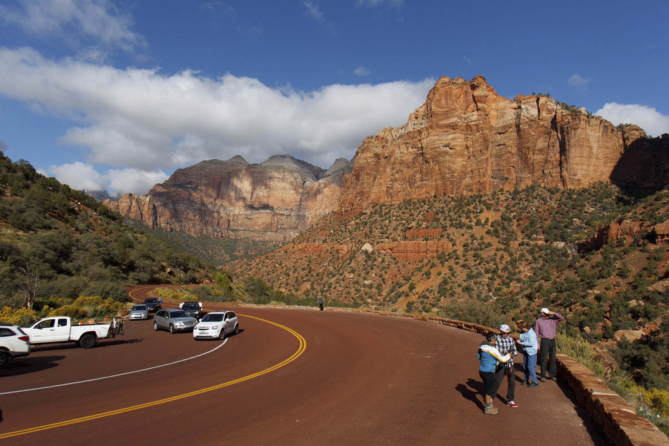 Photo - In this Friday, Oct. 11, 2013 photo, visitors to Zion National Park take in the sights after the park opened on a limited basis. Thousands of hikers, bikers and nature-lovers traveled to Utah's red rock national parks this weekend as they were reopened for the first time since the partial government shutdown began Oct. 1. (AP Photo/The Salt Lake Tribune, Trent Nelson)  DESERET NEWS OUT; LOCAL TV OUT; MAGS OUT