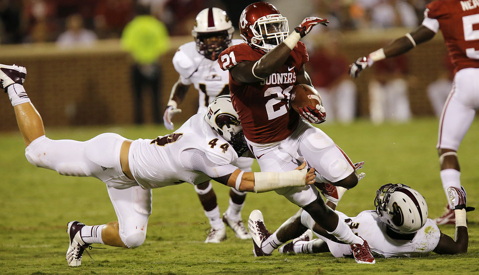 Photo - Oklahoma's Keith Ford (21) runs past Louisiana Monroe's Austin Moss (44) during the college football game between the University of Oklahoma Sooners (OU) and the University of Louisiana Monroe Warhawks (ULM) at the Gaylord Family Memorial Stadium on Saturday, Aug. 31, 2013 in Norman, Okla.  Photo by Chris Landsberger, The Oklahoman