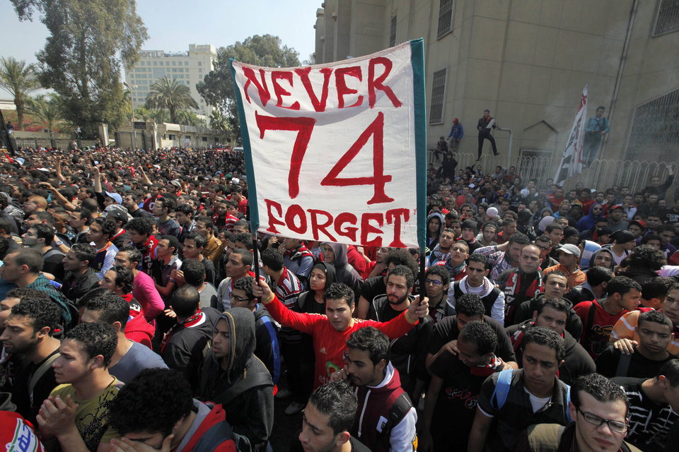 Photo - An Egyptian soccer fan of Al-Ahly club raises a banner honoring fellow fans killed in a 2012 stadium riot in the club headquarters in Cairo, Egypt, Saturday, March 9, 2013. An Egyptian court on Saturday confirmed the death sentences against 21 people for taking part in a deadly soccer riot but acquitted seven police officials for their alleged role in the violence. Suspected fans enraged by the verdict torched the soccer federation headquarters and a police club in Cairo in protest. (AP Photo/Amr Nabil)