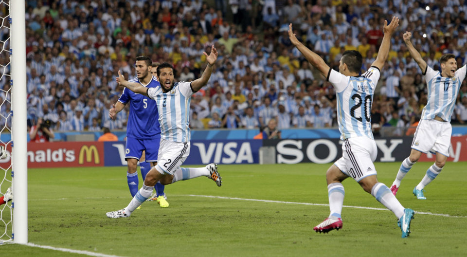 Photo - Argentine players celebrate as Bosnia's Sead Kolasinac (5) looks back after scoring an own goal during the group F World Cup soccer match between Argentina and Bosnia at the Maracana Stadium in Rio de Janeiro, Brazil, Sunday, June 15, 2014. Celebrating are Argentine players Ezequiel Garay (2), Sergio Aguero (20) and Federico Fernandez (17). (AP Photo/Thanassis Stavrakis)