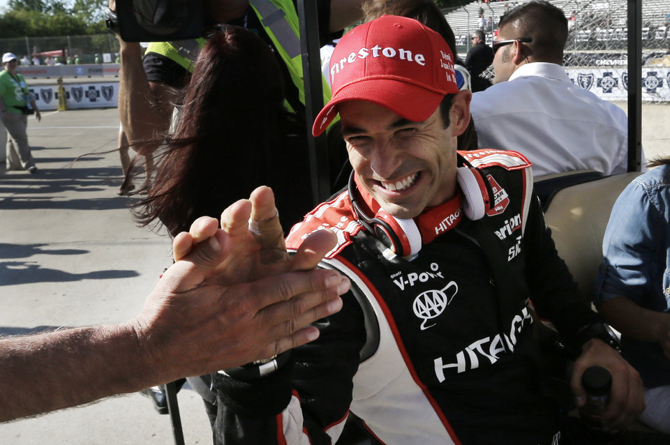 Photo - Helio Castroneves celebrates after winning the second race of the IndyCar Detroit Grand Prix auto racing doubleheader in Detroit Sunday, June 1, 2014. (AP Photo/Paul Sancya)