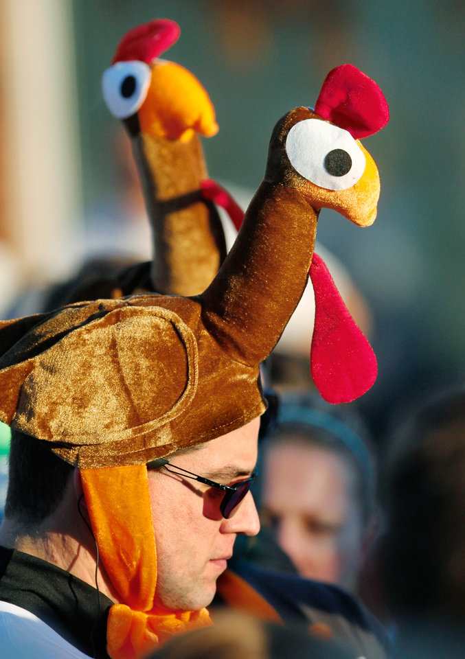 Family members Justin Lowry, Philip Lowry and Josh Martin wear turkey-head hats as they wait with other participants for the start of the 5K run  during the annual Turkey Trot in downtown Edmond Thursday morning,  Nov. 24, 2011.   Photo by Jim Beckel, The Oklahoman