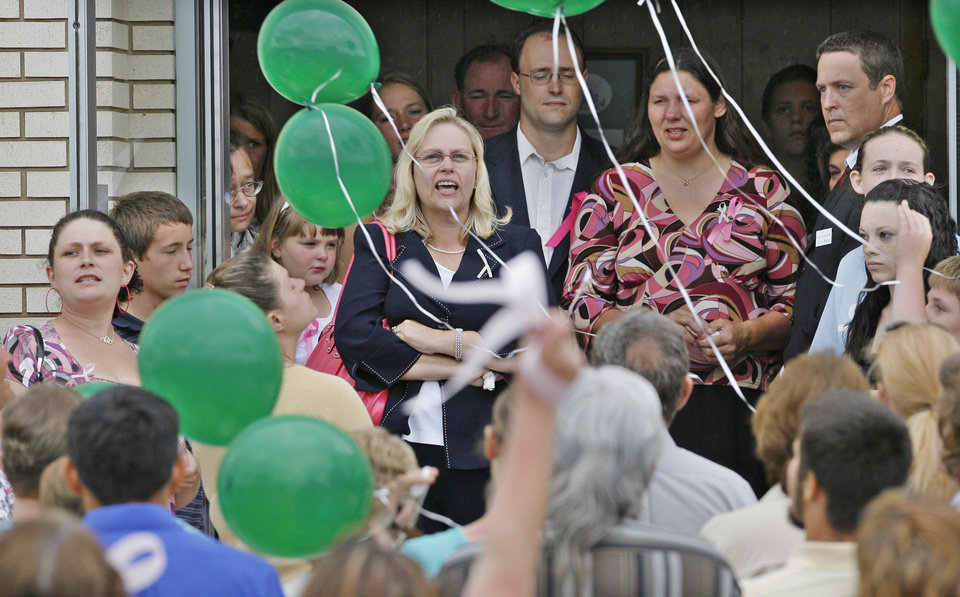 Photo - Principal Wanda Mankin leads the students in a balloon release outside the funeral of Skyla Whitaker in Henryetta, Friday, June 13, 2008. The balloons were released with the crowd saying