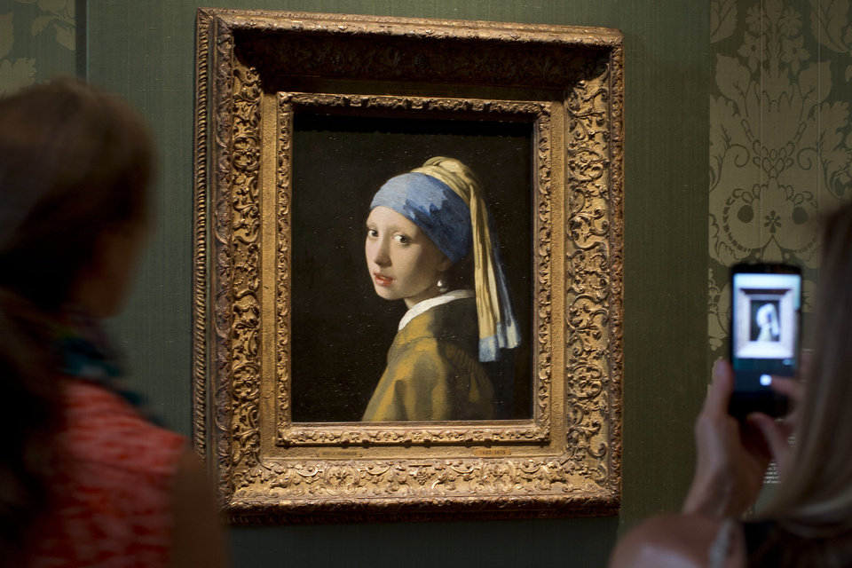 Photo - Visitors take pictures of Johannes Vermeer's Girl with a Pearl Earring (approx. 1665) during a preview for the press of the renovated Mauritshuis in The Hague, Netherlands, Friday, June 20, 2014. The Mauritshuis will open its doors to the public for free from 8 pm till midnight on Friday June 27th after the official ceremonial opening. From June 28 onwards the museum will revert to regular opening hours. (AP Photo/Peter Dejong)