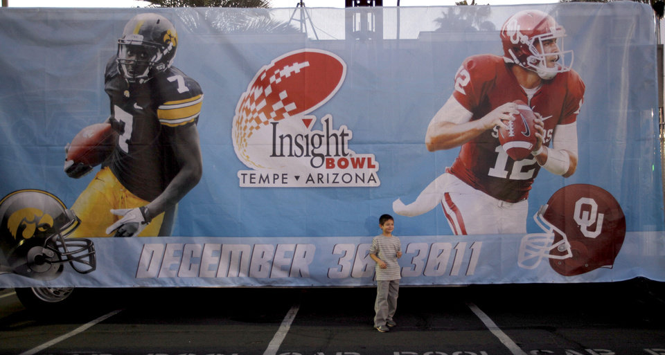 Photo - A fan poses in front of banner before the Insight Bowl college football game between the University of Oklahoma (OU) Sooners and the Iowa Hawkeyes at Sun Devil Stadium in Tempe, Ariz., Friday, Dec. 30, 2011. Photo by Sarah Phipps, The Oklahoman