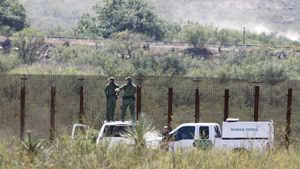Photo -   U.S. Border Patrol agents stand on top of their vehicles and look into Mexico west of Douglas, Ariz., after a Border Patrol agent was shot and killed on Tuesday Oct. 2, 2012. One agent was killed and another wounded in the incident. (AP Photo/Arizona Daily Star, Benjie Sanders) ALL LOCAL TV OUT; PAC-12 OUT; MANDATORY CREDIT