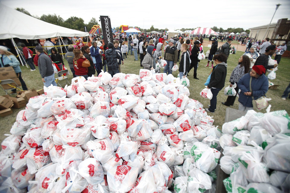 Photo - Piles of groceries are distributed to residents as LOVE OKC and Convoy of Hope distributed goods and services to metro residents Saturday at the old John Marshall High School in Oklahoma City.  Photo by Paul Hellstern, The Oklahoman  PAUL HELLSTERN - Oklahoman