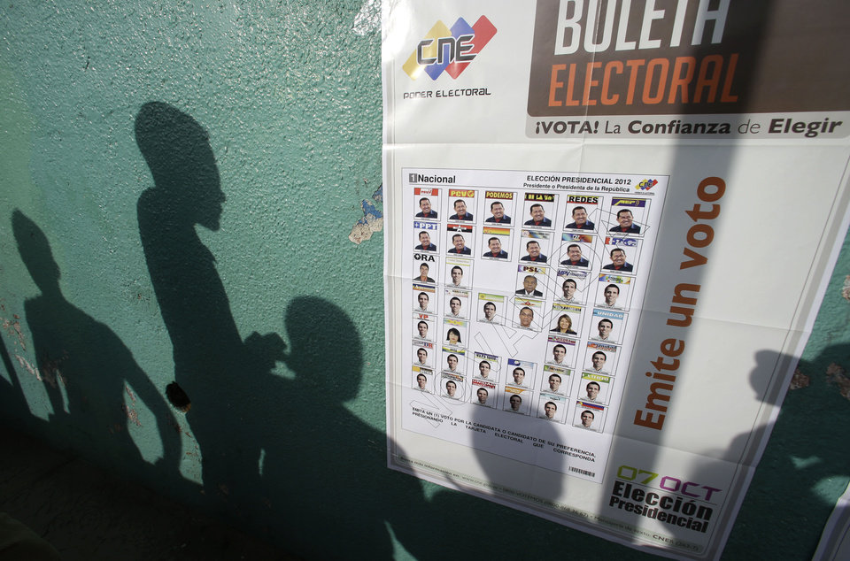 Voters\' shadows are cast on a wall as they wait at a polling station during the presidential election in Caracas, Venezuela, Sunday, Oct. 7, 2012. President Hugo Chavez is running against opposition candidate Henrique Capriles. (AP Photo/Fernando Llano)