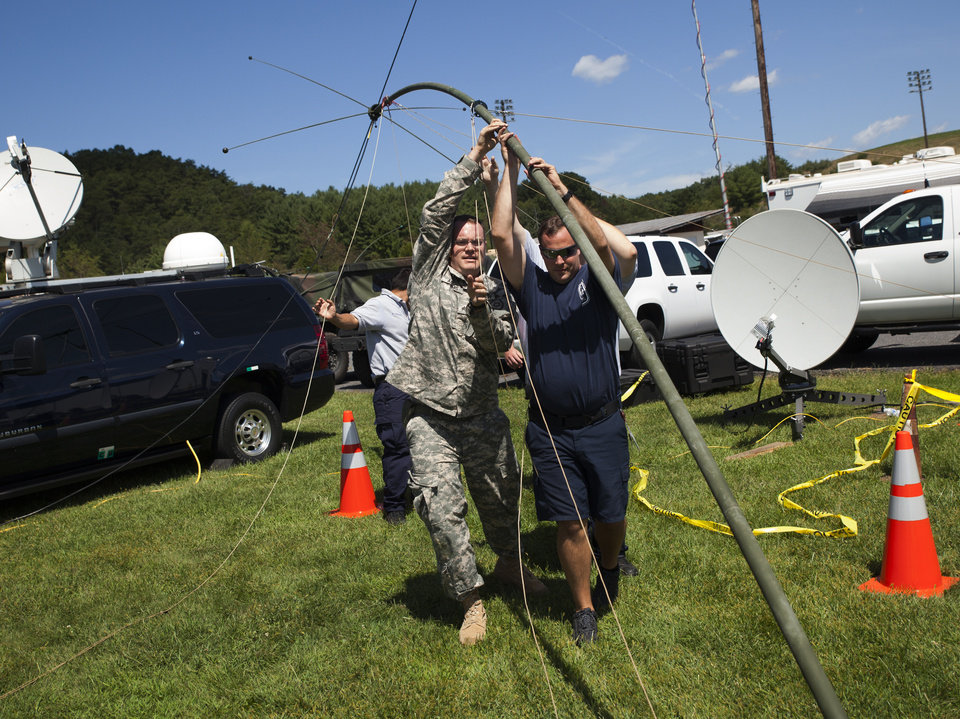 Photo - U.S. Army Sgt. David Adams, left, and a group of firefighters raise a long-range antenna outside the Deerfield Valley Volunteer Fire Department to help communicate with aircraft in the area on Thursday, Aug. 28, 2014 in Deerfield, Va. The pilot of an F-15 jet that crashed this week in remote Virginia mountains was killed, military officials said Thursday, bringing to a sad end an exhaustive two-day search involving more than 100 local, state and federal officials as well as volunteers.  (AP Photo/The Staunton News Leader, Griffin Moores)