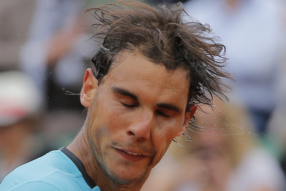 Photo - Spain's Rafael Nadal shakes the sweat off his head after winning his fourth round match of the French Open tennis tournament against Serbia's Dusan Lajovic at the Roland Garros stadium, in Paris, France, Monday, June 2, 2014. Nadal won in three sets 6-1, 6-2, 6-1. (AP Photo/Michel Spingler)