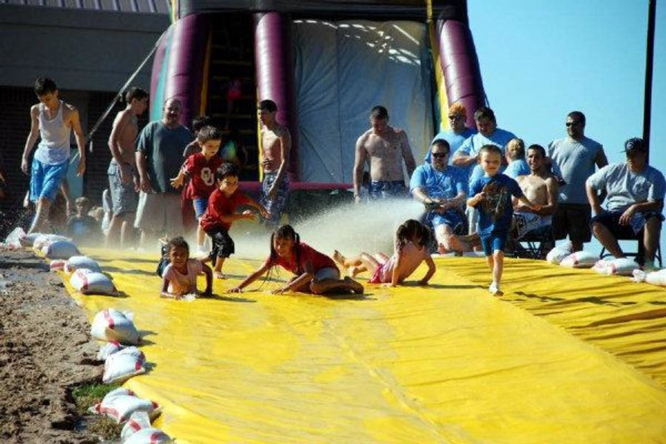Photo - Children take a watery glide down a hill during the 2009 Slip n Slide back to school event at Family of Faith Church in Choctaw. Photo provided.