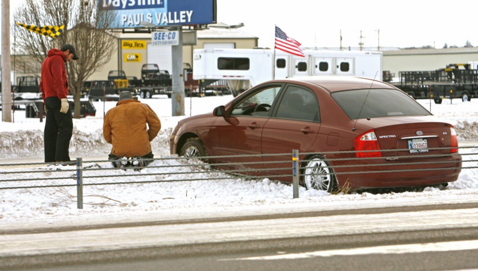 Photo - A motorist gets assistance after skidding into the center median northbound on Interstate 35 south of Norman as ice and snow continue to make roadways slick and hazardous on Thursday, February 3, 2011, in Norman, Okla.  Photo by Steve Sisney