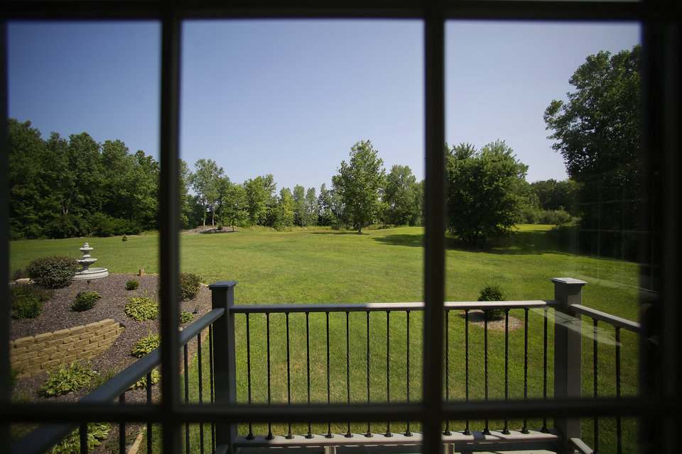 Photo - This is the view of an expansive backyard from inside a luxury home on Wednesday, July 30, 2014, in Springfield, Ill. The home is located near The Rail Golf Course, on the 5 acres of land, next to 66 acres of recreation zoned land and timber. (AP Photo/Seth Perlman)