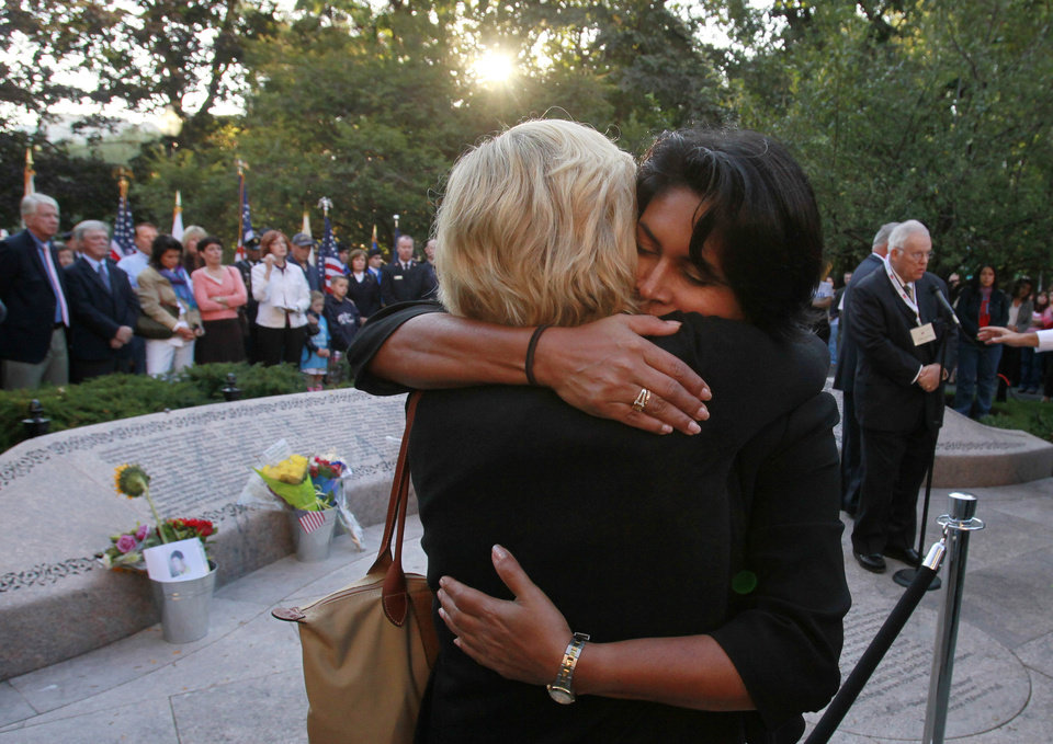 Two women embrace during ceremonies  in the Boston Public Garden in front of a memorial to Massachusetts residents who died on 9/11, on the 10th anniversary of the terrorist attacks, Sunday, Sept. 11, 2011, in Boston. The two planes that crashed into the World Trade Center in New York took off from Boston Logan International Airport. (AP Photo/Michael Dwyer)