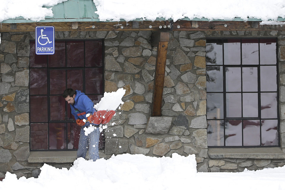 Photo - Sean Nichols clears the walkway of snow at the Rainbow Lodge near Norden, Calif. Friday, Dec. 4, 2015. The first storm of December brought much needed rain to the valley and snow to the Sierra Nevada.(AP Photo/Rich Pedroncelli)