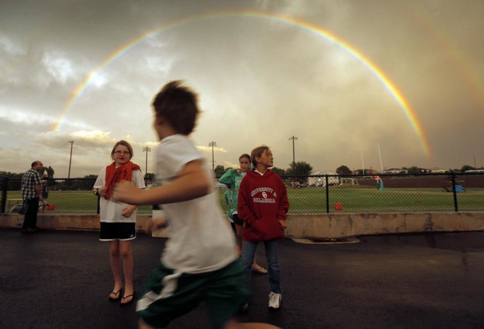 Children play as a rainbow arcs across the sky after a thunderstorm before the high school football game between McGuinness and Douglass at Bishop McGuinness Catholic High School in Oklahoma City, Thursday, Sept. 2, 2010. Photo by Nate Billings, The Oklahoman ORG XMIT: KOD