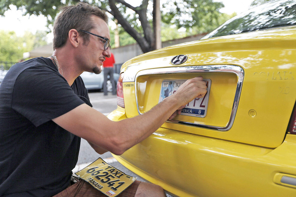 Photo - FILM / MOVIE: Props master Colin Warde changes plates on car on set of