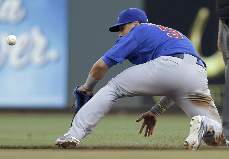 Photo - Chicago Cubs second baseman Javier Baez can't catch a base hit by Cincinnati Reds' Billy Hamilton in the first inning of a baseball game, Wednesday, Aug. 27, 2014, in Cincinnati. (AP Photo/Al Behrman)