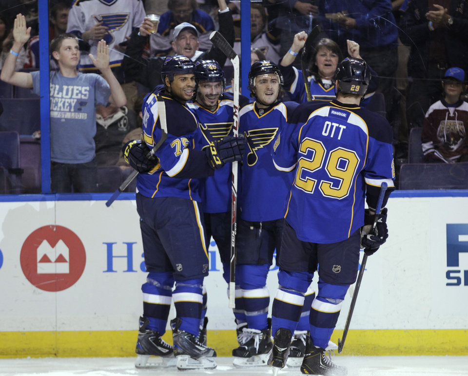 Photo - St. Louis Blues' Maxim Lapierre, second from left, celebrates with teammates after scoring a goal during the second period of an NHL hockey game against the Washington Capitals, Tuesday, April 8, 2014, in St. Louis.(AP Photo/Tom Gannam)