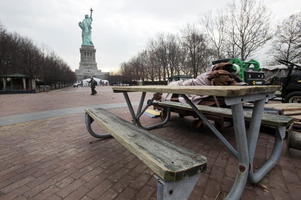 A warped picnic bench sits with other debris on Liberty Island, in New York,  Friday, Nov. 30, 2012. Tourists in New York will miss out for a while on one of the hallmarks of a visit to New York _ seeing the Statue of Liberty up close. Though the statue itself survived Superstorm Sandy intact, damage to buildings and Liberty Island's power and heating systems means the island will remain closed for now, and authorities don't have an estimate on when it will reopen. (AP Photo/Richard Drew)