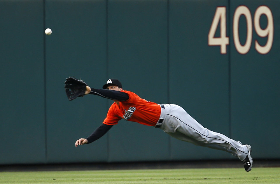 Photo - Miami Marlins center fielder Jake Marisnick dives for a line drive by Philadelphia Phillies' Chase Utley during the first inning of a baseball game, Wednesday, June 25, 2014, in Philadelphia. Marisnick made the catch. (AP Photo/Matt Slocum)