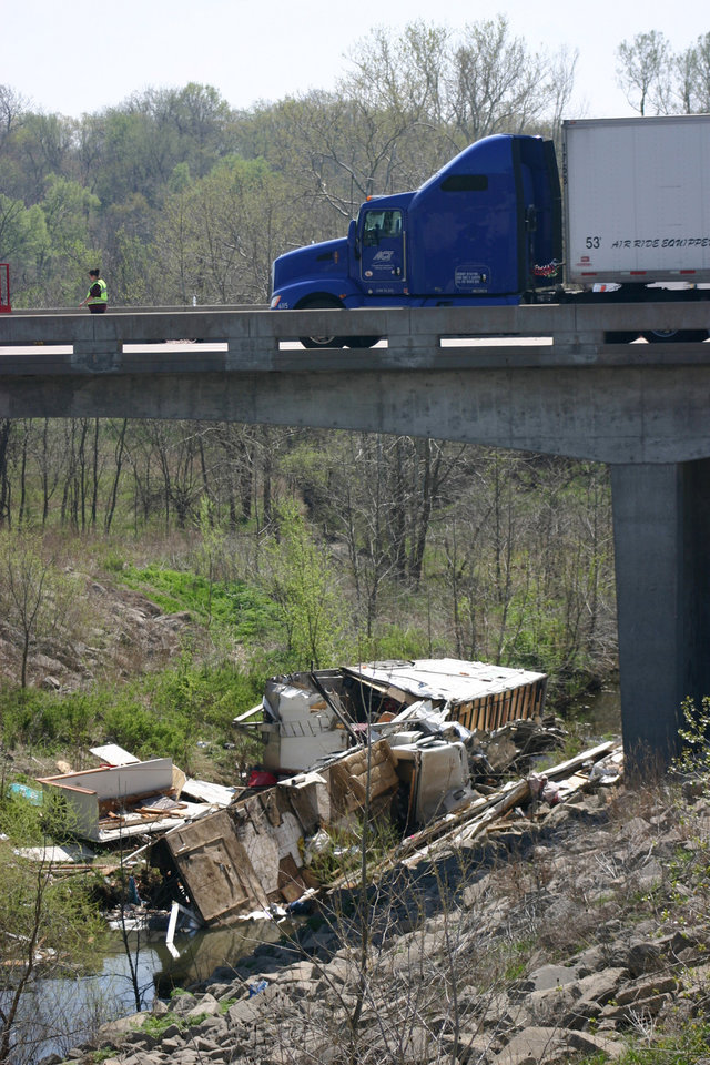 In a Sunday, April 1, 2012 photo, the wreckage of a box truck that was pulling a trailer lies in a ravine after it hit a guardrail and a concrete bridge near Williamsburg, Kan. Authorities said 18 people were inside the vehicle, which had living quarters inside, when it crashed, killing five. A family friend said a Minnesota family and some friends were taking a spring break vacation to see a motocross race. (AP Photo/The Ottawa Herald, Jeanny Sharp) NO SALES (AP Photo/The Ottawa Herald, Jeanny Sharp) NO SALES