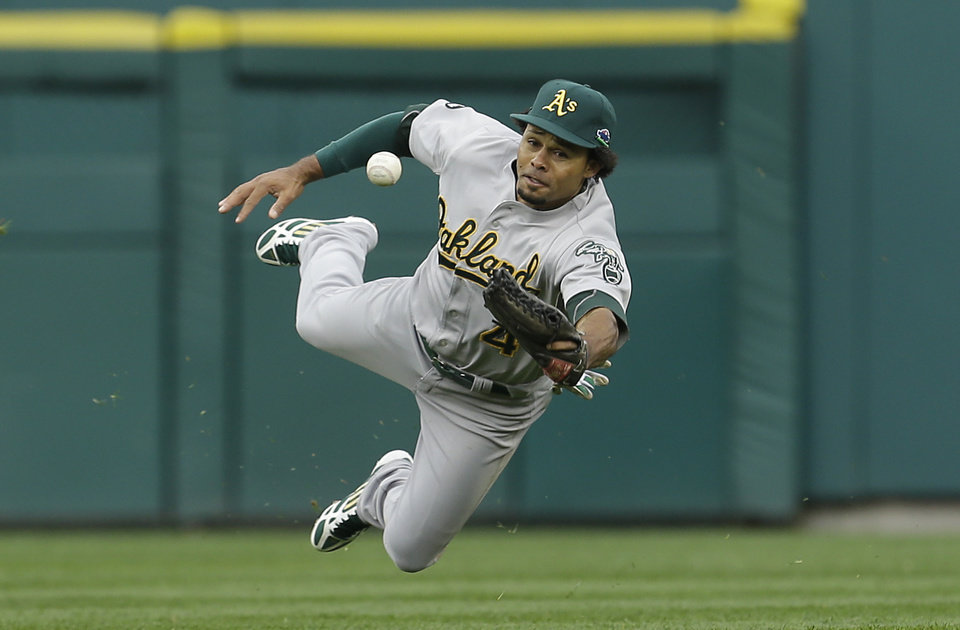 Photo -   Oakland Athletics center fielder Coco Crisp bobbles a hit by Detroit Tigers' Miguel Cabrera allowing Tigers' Austin Jackson and Omar Infante to score during the seventh inning of Game 2 of the American League division baseball series, Sunday, Oct. 7, 2012, in Detroit. (AP Photo/Paul Sancya)