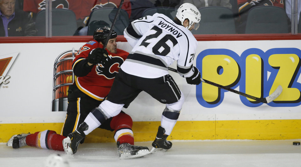 Photo - Los Angeles Kings' Slava Voynov, right, from Russia, checks Calgary Flames' Lance Bouma during the first period of an NHL hockey game in Calgary, Alberta, Monday, March 10, 2014. (AP Photo/The Canadian Press,  Jeff McIntosh)