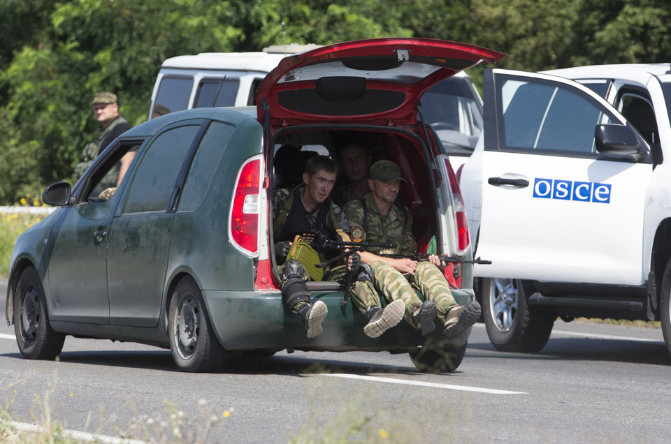 Photo - Pro-Russian rebels travel past a convoy of the OSCE mission in Ukraine outside the city of Donetsk, eastern Ukraine Wednesday, July 30, 2014. (AP Photo/Dmitry Lovetsky)