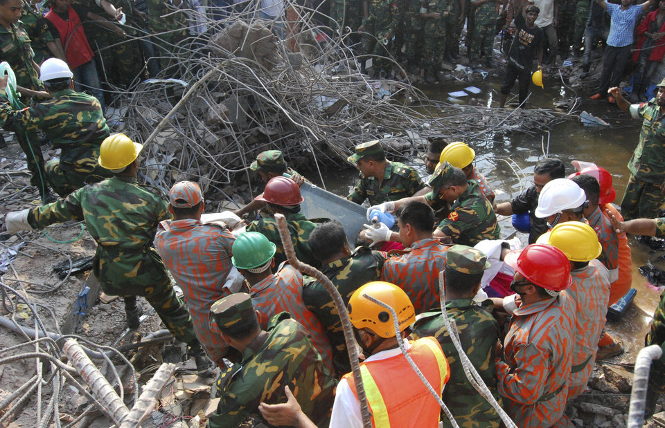 Photo - Rescuers carry a survivor pulled out from the rubble of a building that collapsed in Saver, near Dhaka, Bangladesh, Friday, May 10, 2013. Rescue workers in Bangladesh freed the woman buried for 17 days inside the wreckage of a garment factory building that collapsed, killing more than 1,000 people. Soldiers at the site said her name was Reshma and described her as being in remarkably good shape despite her ordeal. (AP Photo/Parvez Ahmad Rony)