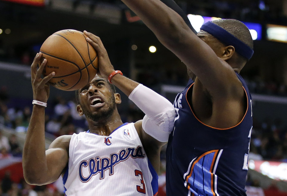 Photo - Los Angeles Clippers guard Chris Paul, left, drives to the basket around Charlotte Bobcats center Brendan Haywood during the first half of an NBA basketball game in Los Angeles, Tuesday, Feb. 26, 2013. (AP Photo/Chris Carlson)