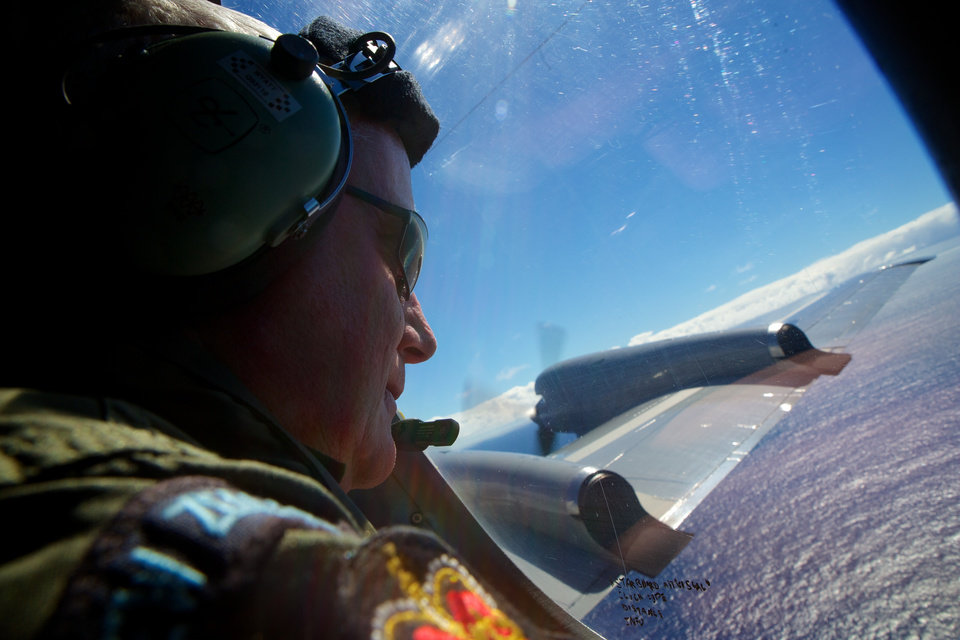Photo - Sgt. Trent Wyatt,  a crew member of a Royal New Zealand Air Force P-3 Orion,  look out in the search for the missing Malaysia Airlines Flight MH370 over the Indian Ocean, Friday, April 11, 2014. Their search area was located 1,800 kilometers (1,125 miles) northwest of Perth and they were tasked with flying at 800 feet to visually search for aircraft debris. Authorities are confident that signals detected deep in the Indian Ocean are from the missing Malaysian jet's black boxes, Australia's Prime Minister Tony Abbott said Friday, raising hopes they are close to solving one of aviation's most perplexing mysteries.  (AP Photo/Richard Wainwright, Pool)