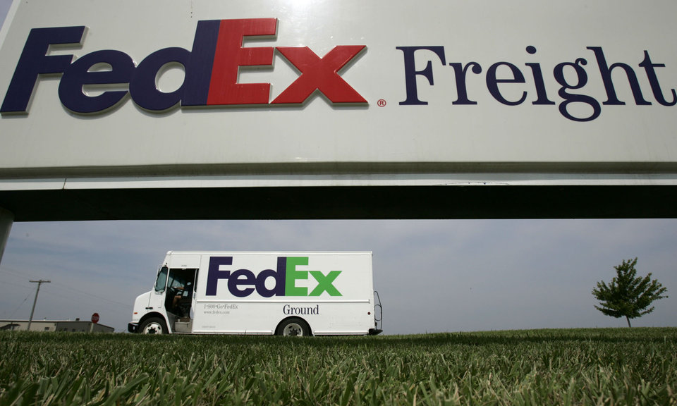 Photo - File - This June 21, 2005 file photo shows a Federal Express delivery truck leaving a FedEx distribution terminal in Edwardsville, Kan. FedEx Corp. is under criminal indictment and facing $1.6 billion in penalties for allegedly failing to police the activities of illegal online pharmacies that use the shipping service to deliver prescription drugs. (AP Photo/Charlie Riedel, File)